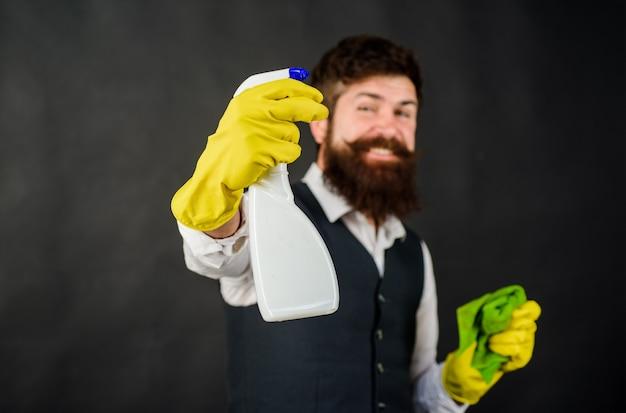 Mannelijke conciërge met reinigingsapparatuur huishoudelijke dienst schonere man met vod en schonere spray