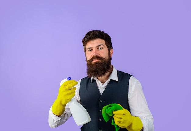 Mannelijke conciërge met reinigingsapparatuur. professionele schoonmaakster in uniform. bebaarde man in uniform, rubberen handschoenen met schoonmaakmiddelen. binnenlandse dienst schonere man met doek en schonere spray.