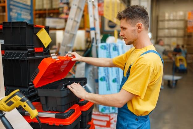 Mannelijke constructor toolbox kiezen in ijzerhandel. bouwer in uniform bekijkt de goederen in de doe-het-zelfwinkel