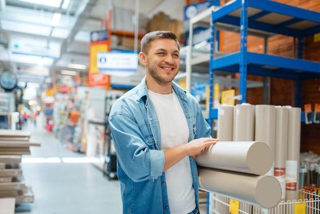 Mannelijke consument die wallpapers in ijzerhandel koopt.