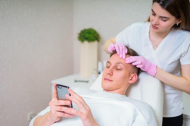 Mannelijke cosmetica. goed uitziende man gezichtsbehandeling ontvangen in luxe spa