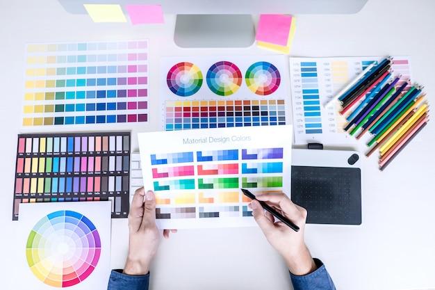 Mannelijke creatieve grafische ontwerper die aan kleurselectie en kleurenmonsters werkt