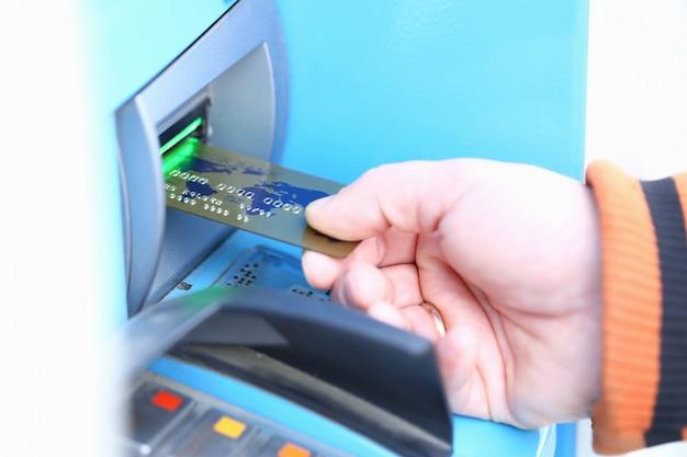 Mannelijke creditcard aganist atm van de handgreep