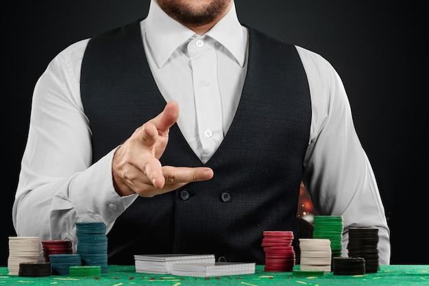 Mannelijke croupier in het casino aan de tafel handen close-up. casinoconcept, gokken, poker, chips op de groene casinotafel.