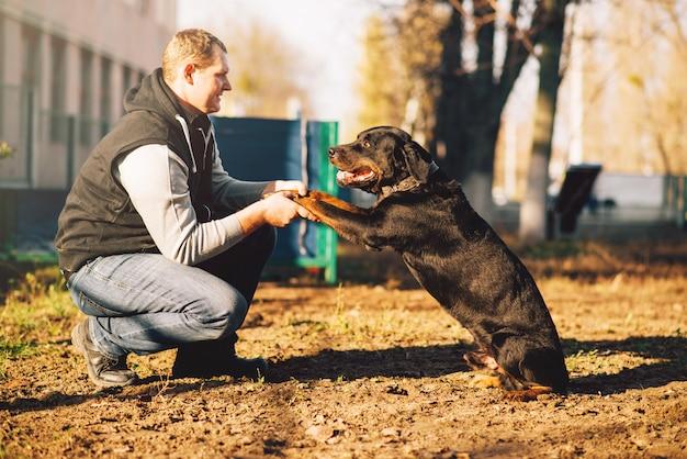 Mannelijke cynoloog, politiehond opleiding buiten. eigenaar met zijn gehoorzame huisdier buiten, bloedhond huisdier