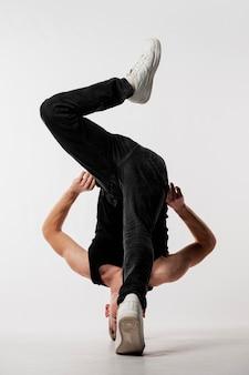 Mannelijke danser in jeans en sneakers poseren met gedraaide lichaam