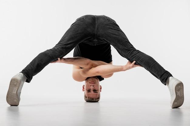 Mannelijke danser in jeans en tennisschoenen die terwijl verdraaid stellen