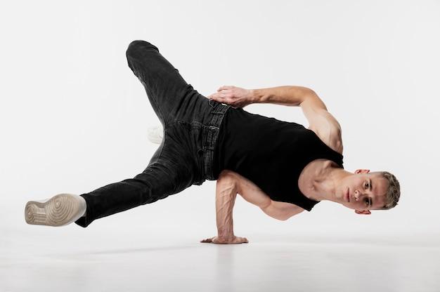 Mannelijke danser in mouwloos onderhemd en jeans die een dansbeweging maken