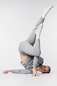 Mannelijke danser in sokken en trainingspak het stellen met omhoog benen