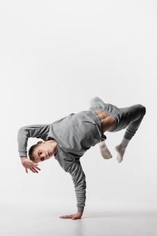 Mannelijke danser in trainingspak dat met exemplaarruimte danst