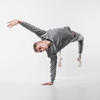 Mannelijke danser in trainingspak en sokken busting een beweging