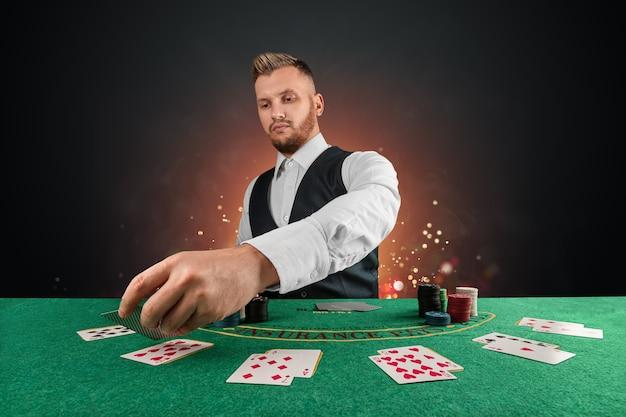 Mannelijke dealer in het casino aan tafel. casinoconcept, gokken, poker, chips op de groene casinotafel.