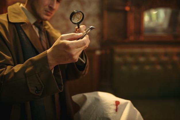 Mannelijke detective kijkt door vergrootglas naar bewijsmateriaal op de plaats delict