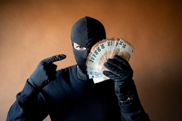 Mannelijke dief met bivakmuts op zijn hoofd die een handvol eurobiljetten voor zijn ogen houdt die op het geld wijzen