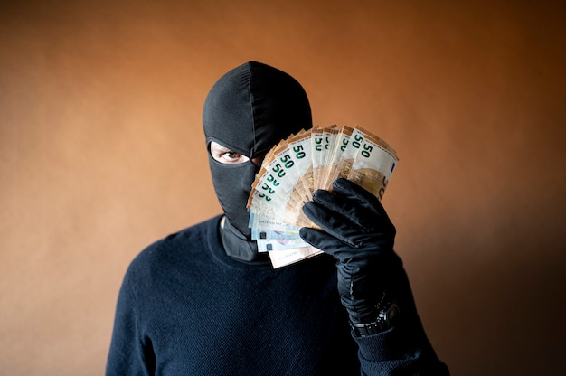 Mannelijke dief met bivakmuts op zijn hoofd die een handvol eurobiljetten voor zijn ogen houdt