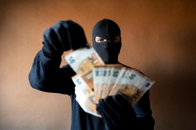 Mannelijke dief met bivakmuts op zijn hoofd met een handvol uitgewaaierde eurorekeningen