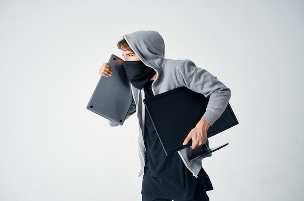 Mannelijke dief misdaad anonimiteit voorzichtigheid bivakmuts lichte achtergrond