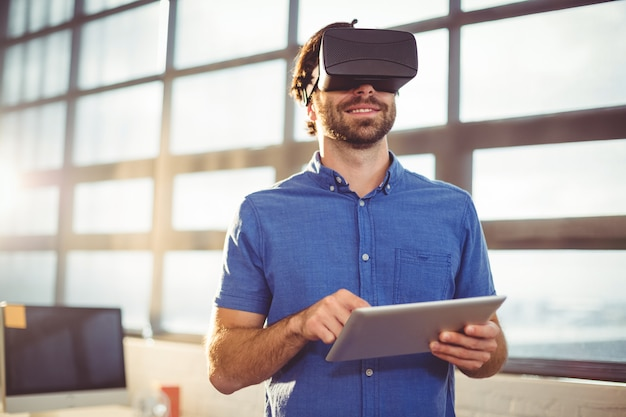 Mannelijke directeur in virtual reality headset met behulp van digitale tablet