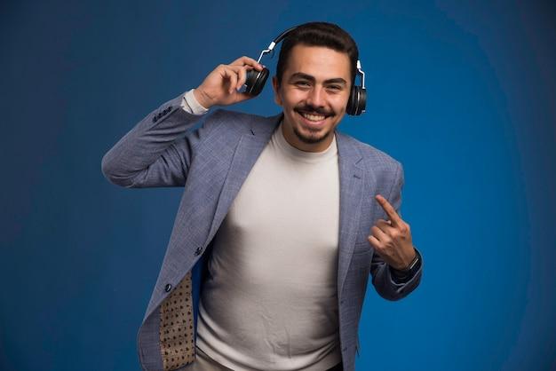 Mannelijke dj in grijs pak koptelefoon dragen en wordt opgewonden.