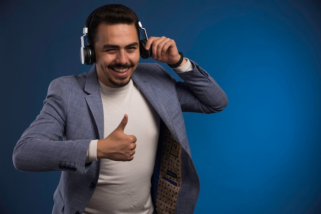 Mannelijke dj in grijs pak koptelefoon luisteren en geniet.