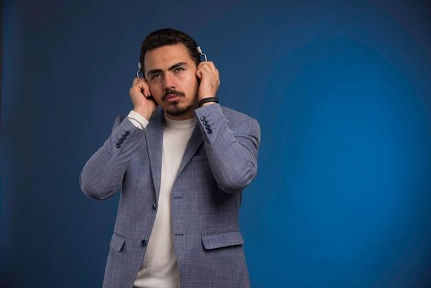 Mannelijke dj in grijs pak koptelefoon luisteren en wordt verrast.