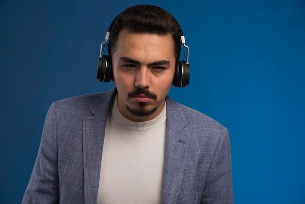 Mannelijke dj in grijs pak luisteren naar koptelefoon en niet genieten van de muziek.