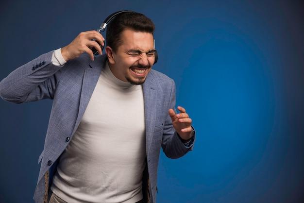 Mannelijke dj in grijs pak luisteren naar koptelefoon met hoog volume.