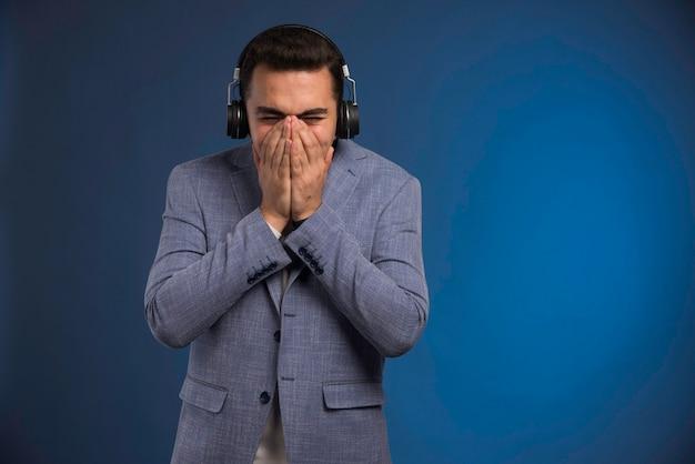 Mannelijke dj in grijs pak luisteren naar koptelefoon.