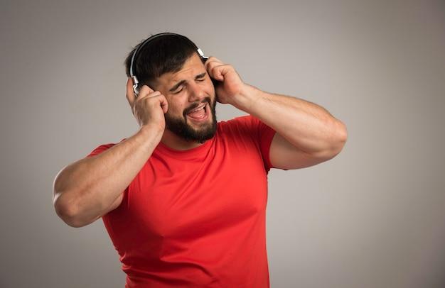 Mannelijke dj in rood shirt hoofdtelefoon dragen en zingen.
