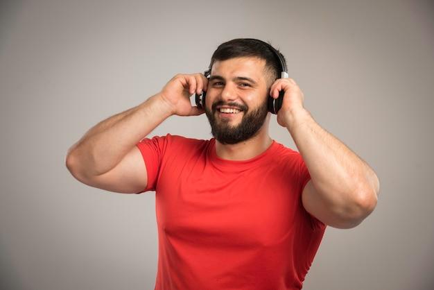 Mannelijke dj in rood shirt koptelefoon dragen en luisteren naar muziek terwijl u ontspant.