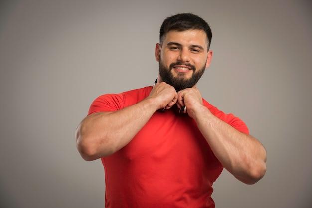 Mannelijke dj in rood shirt met koptelefoon in de nek met plezier