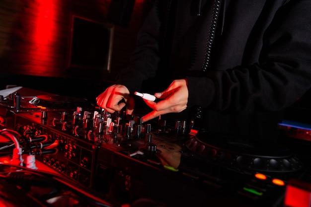 Mannelijke dj's hand draait bekers en houdt elektronische sigaret vast. close-up shot. nachtleven concept. man muziek afspelen op feestje in nachtclub. donkere sfeer.