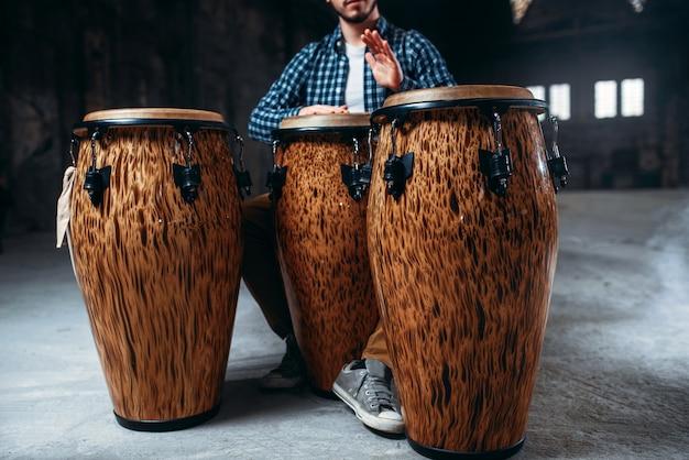 Mannelijke drummer speelt op houten drums in fabriekswinkel