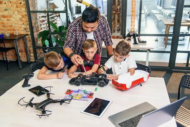 Mannelijke elektronische ingenieur met europese schoolkinderen die in slim schoollaboratorium werken en model van radiografisch bestuurbare elektrische auto testen.