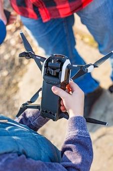 Mannelijke en kinderhanden die drone houden en een drone in het park gaan starten
