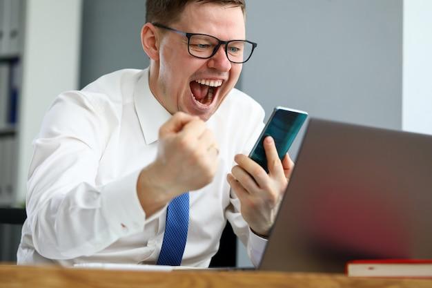 Mannelijke en manager die terwijl het bekijken smartphoneportret gillen articuleren. online inzetten of casino. teambuilding en motivatie op afstand terwijl coronavirus concept in quarantaine-periode plaatst