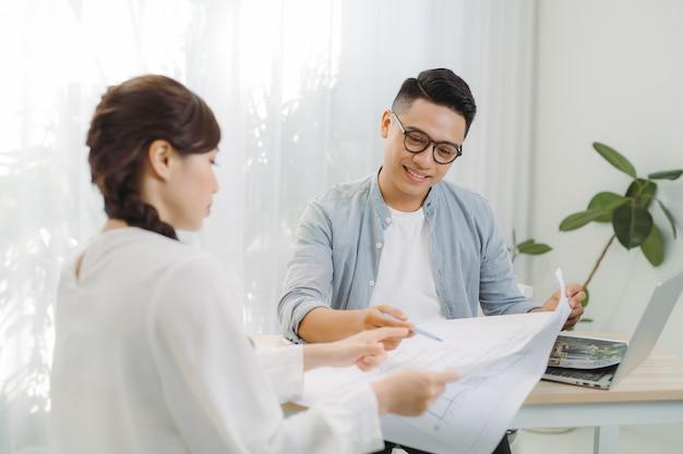 Mannelijke en vrouwelijke architect die een reeks blauwdrukken bespreken die op een lijst op kantoor worden uitgespreid.