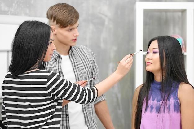 Mannelijke en vrouwelijke artiesten die make-up doen voor model in salon