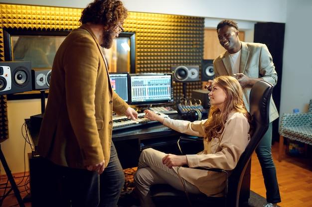 Mannelijke en vrouwelijke artiesten, opnamestudio interieur op de achtergrond. synthesizer en audiomixer, muzikantenwerkplek, creatief proces