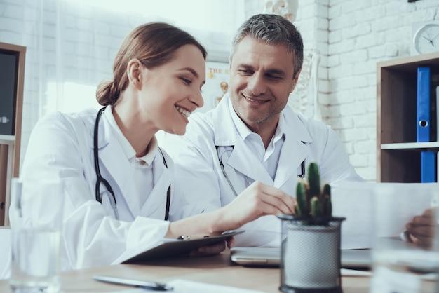 Mannelijke en vrouwelijke artsen in witte toga's met stethoscopen