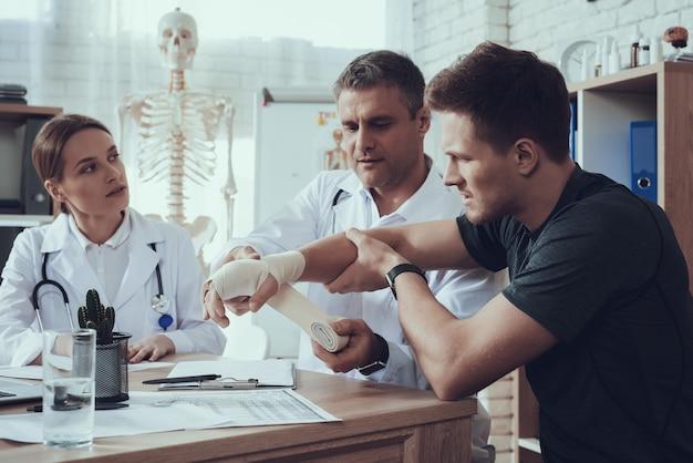 Mannelijke en vrouwelijke artsen met de hand van de basketbalspeler doen pijn