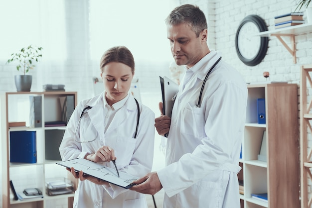 Mannelijke en vrouwelijke artsen met stethoscopen in kantoor. artsen vergelijken aantekeningen.