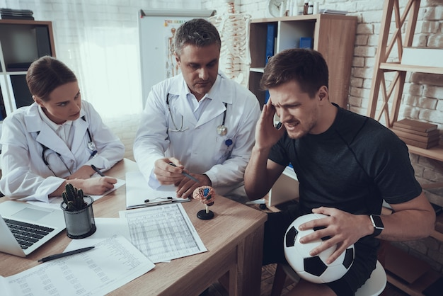 Mannelijke en vrouwelijke artsen met stethoscopen in kantoor met voetballer.