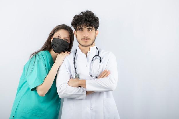 Mannelijke en vrouwelijke artsen staan en kijken naar de camera.