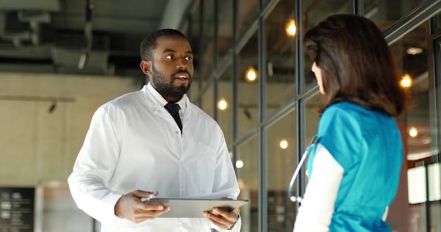 Mannelijke en vrouwelijke artsen van gemengde rassen praten vrolijk in de kliniek. multi-etnische man en vrouw, medici met discussie in het ziekenhuis. arts met verpleegster. doc en assistent. gesprek. achter.