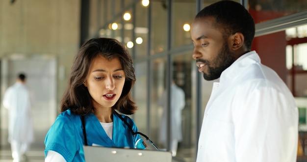 Mannelijke en vrouwelijke artsen van gemengde rassen vreugdevol praten in de kliniek. multi-etnische man en vrouw, medici met discussie in het ziekenhuis. arts met verpleegster. doc en assistent. gesprek.