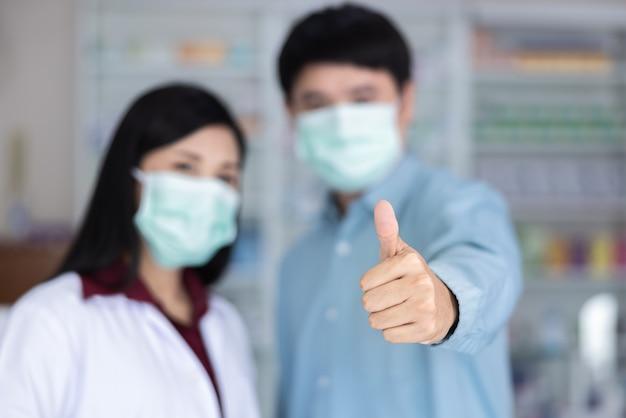 Mannelijke en vrouwelijke aziatische apotheker beschermt door beschermend masker en duim omhoog te gebruiken in drogisterij thailand selectieve focus op hand coronavirus en covid-19 concept