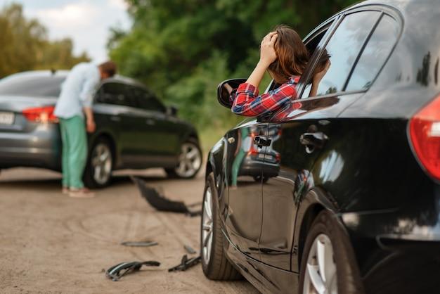 Mannelijke en vrouwelijke chauffeurs na auto-ongeluk op de weg