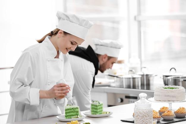Mannelijke en vrouwelijke chef-koks die in de keuken werken