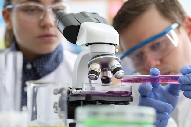 Mannelijke en vrouwelijke chemicus onderzoek roze vloeistof